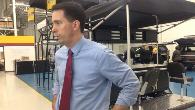 Gov. Scott Walker fields questions from reporters Monday after his tour of the C TECH Manufacturing facility in the village of Weston.