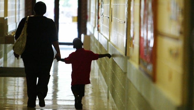 Angel Iglus walks her son to a classroom at Myrtle Place Elementary on the first day of school in 2011. Myrtle Place has one of the lowest absenteeism rates in the parish, according to Associated Press data.