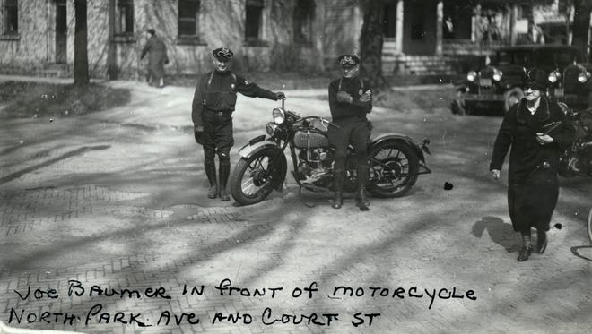 People Watching, 1920s: Two patrol officers stand near the Sandusky County Courthouse by their motorcycle in this interesting early photograph, which looks toward the northeast corner of Park Avenue and Court Street in Fremont. Notice the patched brick pavement in the foreground. The corner building and house behind them are still standing today.