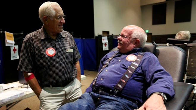 Bob Koenig, 73, of Stayton, right, talks with American Cross volunteer Larry Gower before donating blood for the 100th time for the American Red Cross at Foothills Methodist Church in Stayton, Ore., on Monday, Nov. 16, 2015.