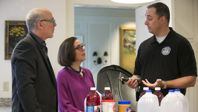 Andrew Phelps, Director for the state Office of Emergency Management, talks to Governor Kate Brown and First Gentleman Dan Little at Mahonia Hall about the first week's supplies to add to their personal preparedness kit for the Cascadia Subduction Zone earthquake.