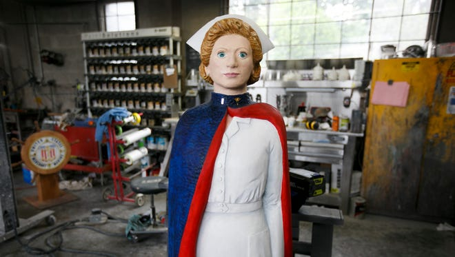 A carving of an Army nurse, painted by Shari Watkins and carved by Carole Duree-Jones, in Vista Body Shop in Salem on Thursday, June 23, 2016. Vista is applying a clear top coat to six wooden figures, carved and painted by local artists to represent different branches of the military. The carvings will temporarily replace the traditional figures in Mt. Angel's Glockenspiel beginning July 4.