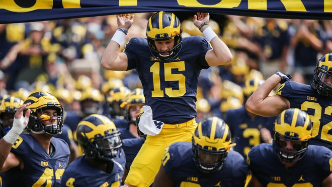 """Michigan Wolverines players enter the field and touch the """"Go Blue"""" banner Saturday, Sept. 3, 2016."""