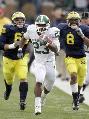 Michigan State's Javon Ringer races away from Michigan's Mike Martin and Jonas Mouton, right, for a touchdown in the second quarter on Saturday, October 25, 2008, at Michigan Stadium in Ann Arbor.