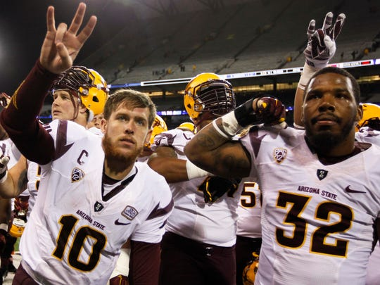 Taylor Kelly celebrates with Antonio Longino following a 24-10 ASU win over Washington in Seattle on Oct. 25, 2014.