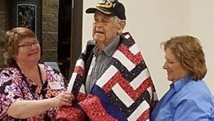Marshfield World War II veteran Don Krasin (center) stands under his Quilt of Valor, presented by Karen Demaree (right), the state coordinator of the Quilts of Valor Foundation. Krasin's niece, Pat Nennig, helps Krasin with the quilt.