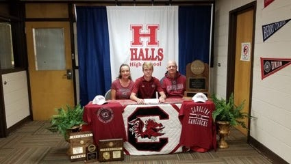 Ryan Hall, center, poses with his parents at a National Signing Day ceremony at Halls High School on Wednesday, Nov. 8, 2017. He will play golf at South Carolina.