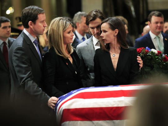 Jenna Bush Hager, second from left, her husband Henry Hager, left, her twin sister Barbara Bush, right, and Barbara's husband Craig Coyne, second from right, gather around the flag-draped casket of their grandfather, former President George H.W. Bush as he lie in state at the U.S. Capitol in Washington, Tuesday, Dec. 4, 2018. (AP Photo/Manuel Balce Ceneta)