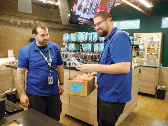 Bud tender Bryan Keith , left, and lead bud tender Sonny Palmer of the Agate Dreams recreational cannabis business  get product for a customer at the Suquamish Tribe  on Friday.