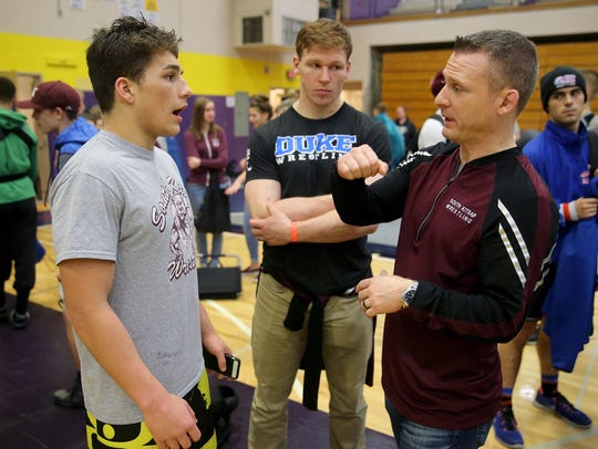 South Kitsap head coach Chad Nass (right) talks to wrestler Sebastian Robles during the South Puget Sound League 4A tournament.
