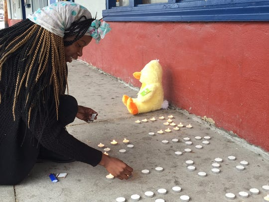 Nicole Murray, 26, was lights candles at a makeshift memorial for a homicide victim she only identified as Mace.