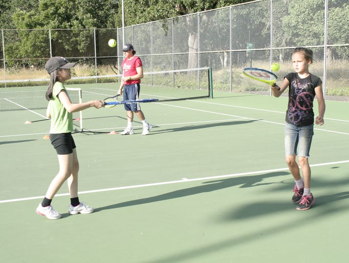 Mindy Altschul (left) and Mackenzie Griswold warm up before their lesson during QuickStart Tennis on July 3 at Bush Ôs Pasture Park tennis courts.