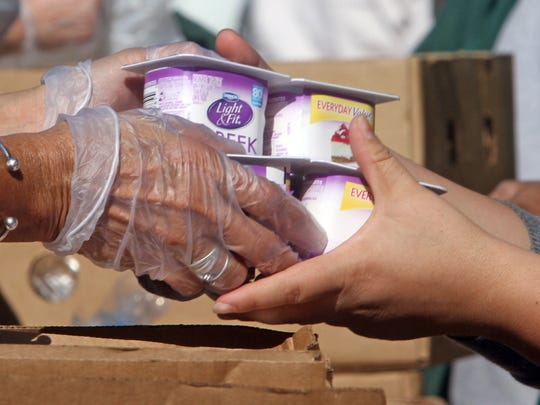 A volunteer hands yogurt to a recipient as over 120 families received food as the Food Bank of Westchester's mobile pantry distributed donated food outside the White Plains library Oct. 21, 2015. The Food Bank has seen a decrease in donations through its retail recovery program due to the A&P closing all its stores.  The A&P had donated thousands of pounds of fresh food each year.