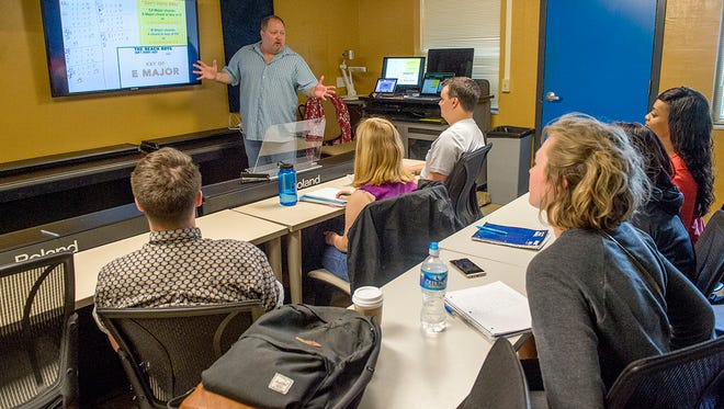 "MTSU assistant professor Odie Blackmon, standing, discusses songwriting techniques with commercial songwriting students in his Ezell Hall classroom in this file photo. MTSU's recording industry program has been included in The Hollywood Reporter's ""Top 25 Music Schools"" list for a second year."