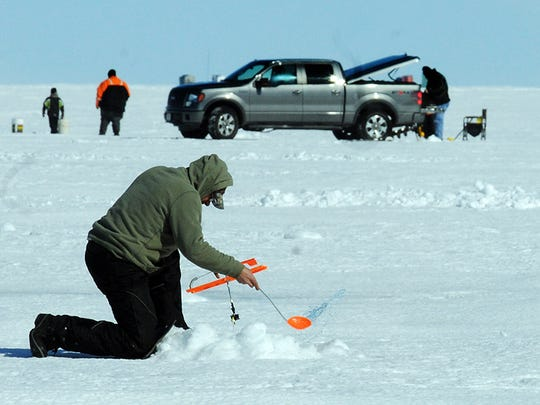Jerry LeMere of Brussels, Door County, uses a slush dipper to clear slush from a fishing hole off LIttle Sturgeon in 2014.