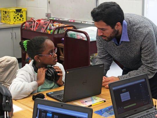 Fatima Ali, 11, gets help from musician Henry Cardenas