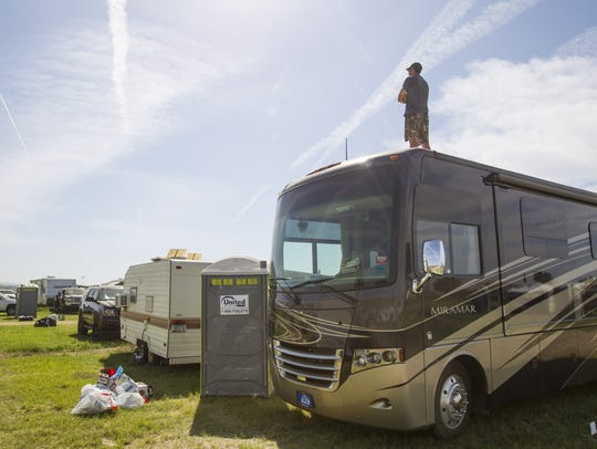A camper stands on top of his RV after the Country