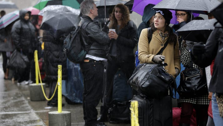 Travelers wait in line, in the rain, to board buses