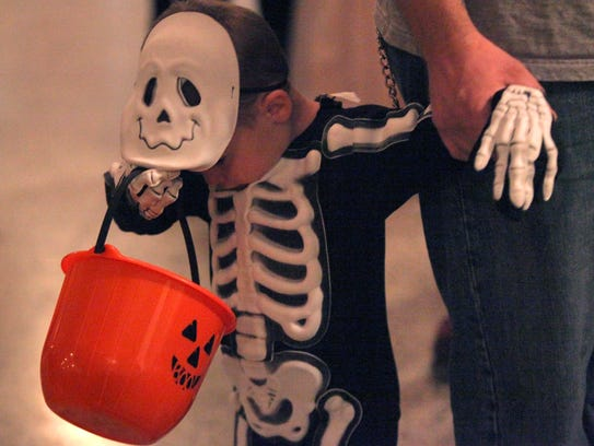 A little skelton checks his candy bucket at a past