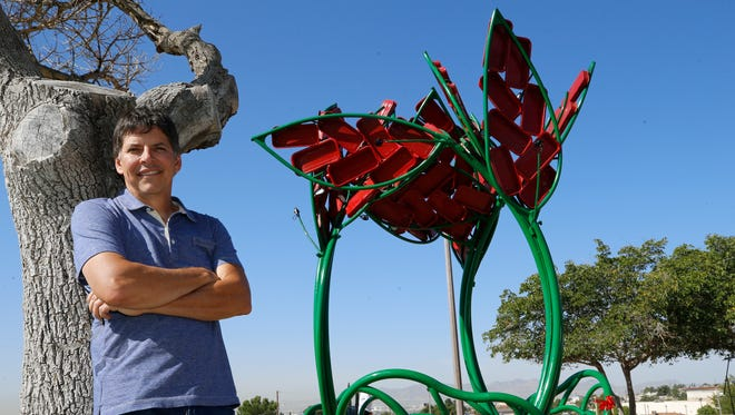 """Sculptor Christopher Fennell stands next to his latest work, """"Wagon Sprouts,"""" at Travis White Park in East Central El Paso."""