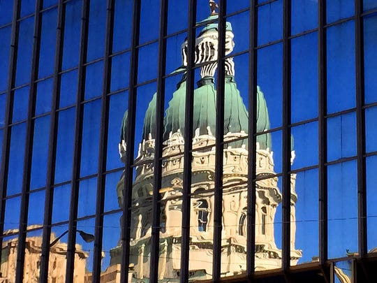 The Indiana Statehouse reflected in a Downtown building on March 30, 2015.