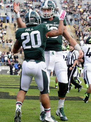 Michigan State quarterback Connor Cook, right, congratulates Michigan State running back Nick Hill (20) on a touchdown during the first quarter against Purdue in an NCAA college football game in West Lafayette, Ind., Saturday, Oct. 11, 2014.