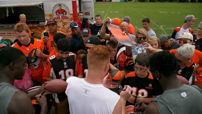 Cincinnati Bengals quarterback Andy Dalton (14) signs autographs for fans after practice on Day 13 of training camp at the Paul Brown Stadium practice facility in downtown Cincinnati on Wednesday, Aug. 10, 2016. The Bengals and Vikings met on the practice field for the first of two joint practices ahead the first pre-season game of the year.
