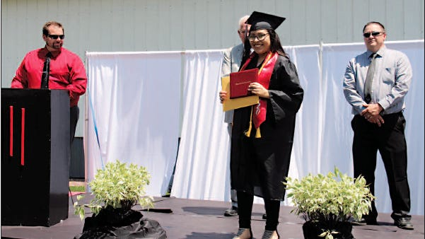 Jennifer Perez beams as she shows off her hard-earned diploma.