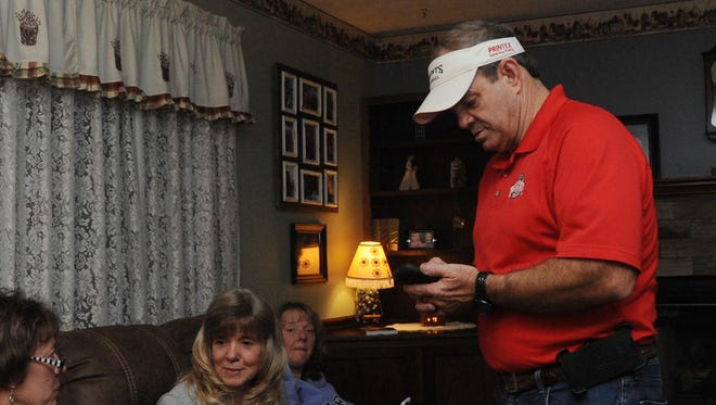 George Lavender, right, checks results on his phone with family and friends Tuesday at his home in Chillicothe.