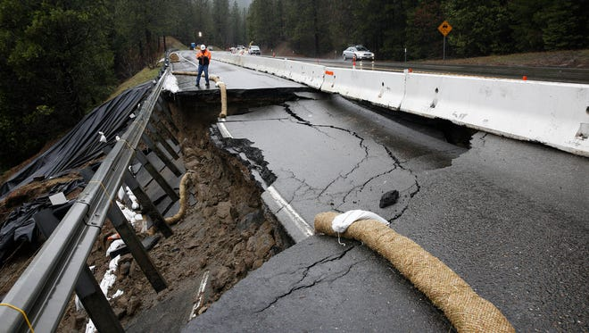 In this Feb. 21, 2017, file photo, the shoulder and one lane of westbound Highway 50 are damaged due to storms near Pollock Pines, Calif. The bill to repair California's roadways hammered by floods and rockslides in an onslaught of storms this winter is already at least $550 million, more than double what the state budgeted for such emergencies.