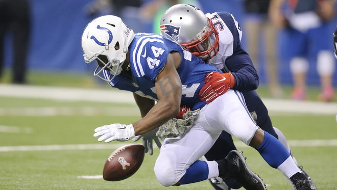 Colts running back Ahmad Bradshaw loses the ball in the second half after being hit by New England Patriots outside linebacker Jamie Collins. Indianapolis hosted New England at Lucas Oil Stadium on Sunday, November 16, 2014.