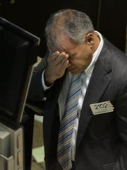 Louis Spina looks distressed as he walks the floor of the New York Stock Exchange in 2007. Spina spiraled after leaving Wall Street, defrauding people through a private trading venture and then robbing a Florida bank.