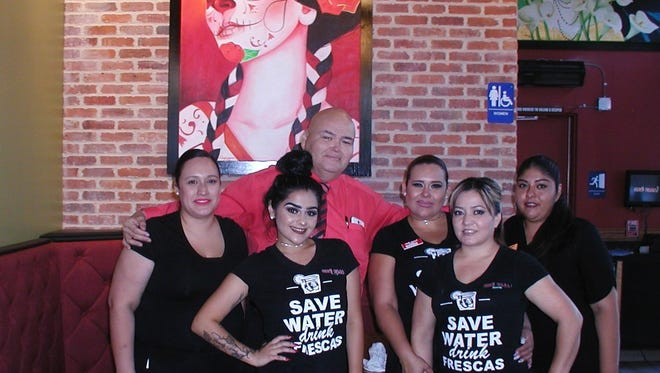 Gabriel Chavez, supervisor  of the new Que Pasa café and bar in Visalia gathers day shift managers and servers for a photo under the watchful gaze of a painting of Catrina, the elegant lady skeleton.