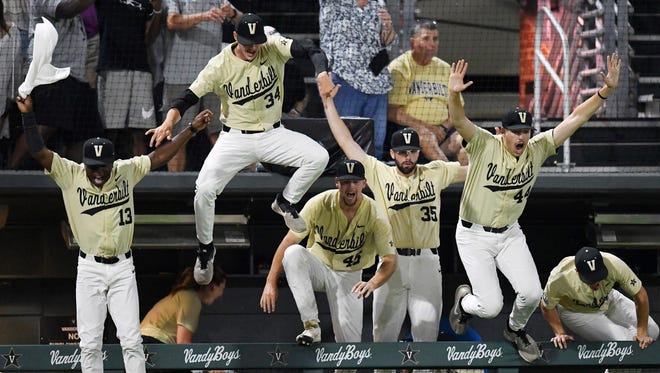 Vanderbilt players leap out of the dugout to celebrate with J.J. Bleday (not shown) after his walk-off home run to win the game 4-3 just after midnight Sunday.