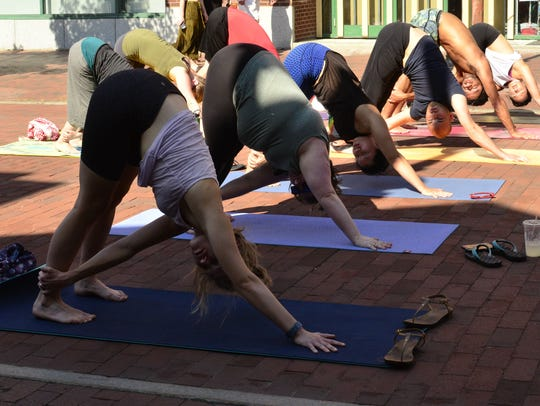 Participants in a yoga class on Church Street on June