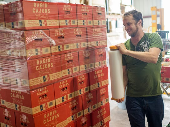 Louis Michot wraps boxes of Ragin' Cajuns beer on a
