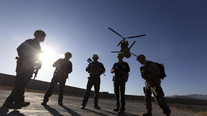 In this Nov. 30, 2017 file photo, American soldiers wait on the tarmac in Logar province, Afghanistan. Top officials in the White House were aware in early 2019 of classified intelligence indicating Russia was secretly offering bounties to the Taliban for the deaths of Americans, a full year earlier than has been previously reported.