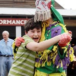 """Leo Hackney, 10, laughs while dancing with a costumed """"Mardi Gras"""" as Vermilionville and the Basile Mardi Gras Association hold a traditional courier de Mardi Gras Sunday at Vermilionville in Lafayette."""