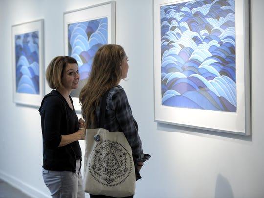 Gallery director Melannie Chard, left, and Cassie Clark discuss Jon Strand's artworks.