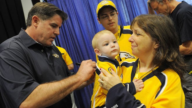 New Predators coach Peter Laviolette made his debut in Nashville at Music City Sportsfest at Music City Center and also signed 9-month-old Benjamin Spraggins' jersey as his grandmother Grace Vircik holds him up.