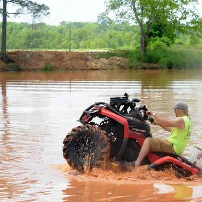 In this file photo, a driver rides his ATV in the mud