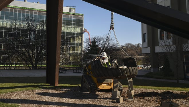 Zack Lahring, with the Tridonn Construction Company, works to reinstall the Motu Viget tire swing in Grand Rapids on March 29, 2016.
