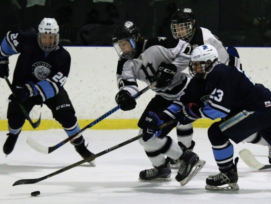 Vying for a loose puck Wednesday at Arctic Edge Arena