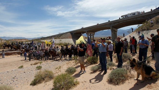 In this April 12, 2014, file photo, the Bundy family and their supporters gather together under the Interstate 15 highway overpass just outside of Bunkerville, Nev., in order to confront the Bureau of Land Management and demand the release of their impounded cattle.