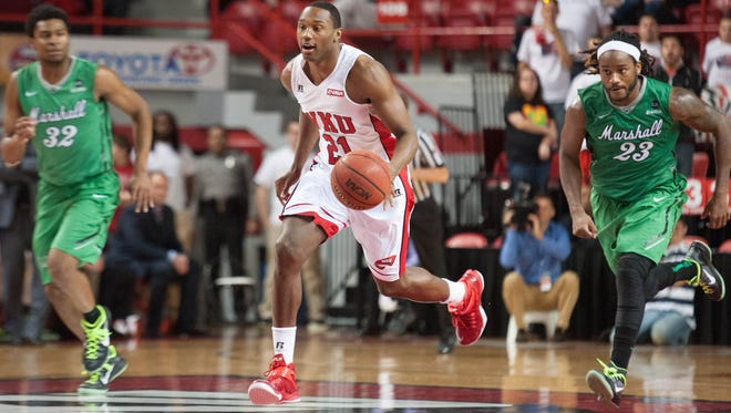 Jan 4, 2015; Bowling Green, KY, USA; Western Kentucky Hilltoppers forward Nigel Snipes (21) drives the ball away from Marshall Thundering Herd guard Tamron Manning (32) and guard Justin Edmonds (23) during the second half at E.A. Diddle Arena. Mandatory Credit: Joshua Lindsey-USA TODAY Sports
