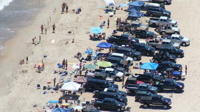 An undated DNREC photo shows trucks and SUVs double-parked on one of the state park beaches where drive-on surf fishing is allowed. A rule change imposed this week ends this practice, requiring surf fishermen to park single-file.