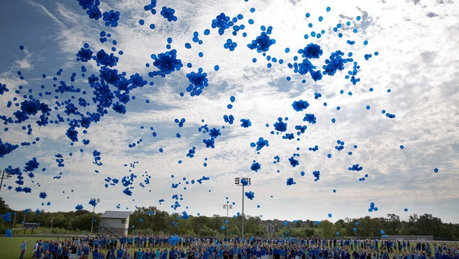 In this Saturday, Sept. 3, 2016, photo, community members release blue balloons while standing in the formation of a heart during a Love for Lane Celebration on what would have been Lane Graves' third birthday, in Omaha, Neb. The parents of the toddler who was killed by an alligator at Walt Disney World in Florida said they will always remember their sweet little boy. (Rebecca S. Gratz/Omaha World-Herald via AP)