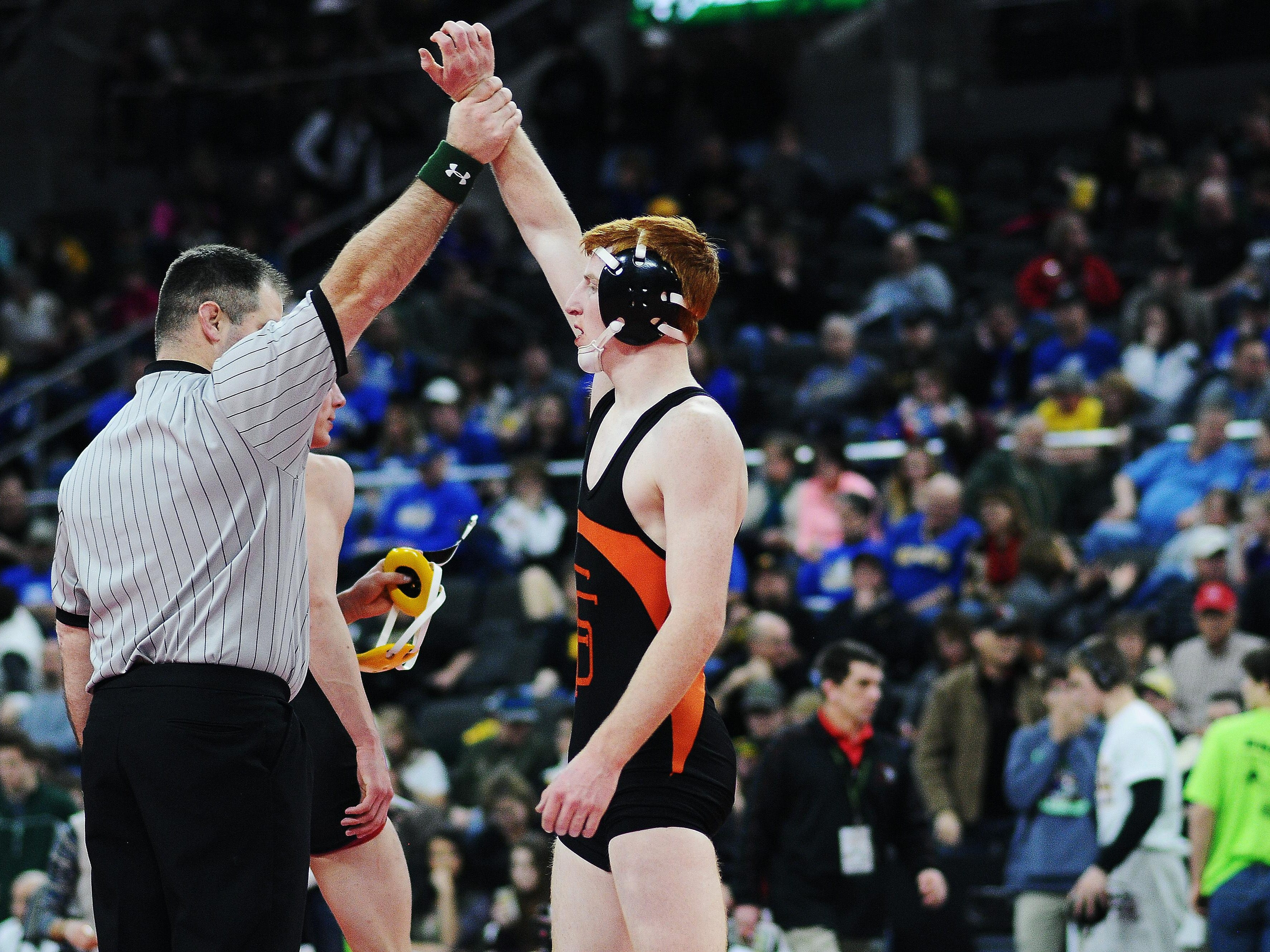 """An official holds up the arm of Washington's Hunter O'Connor after he defeated Roosevelt's Carter Lohr during a 132-pound weight class match during the SDHSAA South Dakota State Class """"A"""" Wrestling Tournament on Friday, Feb. 27, 2015, at the Denny Sanford Premier Center in Sioux Falls, S.D."""