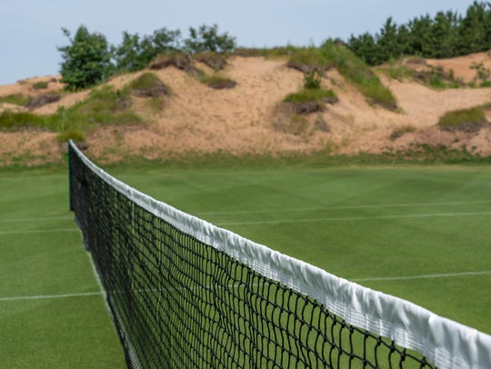 A tennis net overlooks the sand dunes at Sand Valley