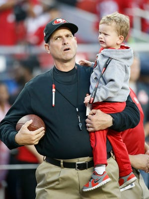 San Francisco 49ers head coach Jim Harbaugh holds his son Jack before an NFL football game against the Seattle Seahawks in Santa Clara, Calif., Thursday, Nov. 27, 2014.
